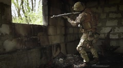 Soldier in the burned a room aiming a machine gun and looking through binoculars Stock Footage
