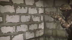 A soldier with a gun is near the brick wall Stock Footage