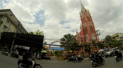 Ho Chi Minh City - Street view with motorbike traffic in front of pink church. Stock Footage