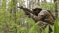 Soldier in camouflage with a gun and moves through the forest - stock footage