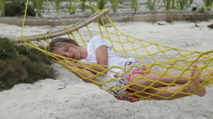 Young girl relaxing in a hammock on the sea beach - stock footage