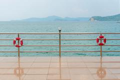 red Lifebuoy on railing by the sea - stock photo