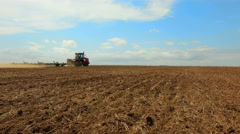 HD aerial footage of a modern tractor plowing dry field, preparing land for Stock Footage