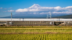 Shinkansen Bullet Trains passing harvested fields and Mount Fuji, Honshu, Japan - stock footage