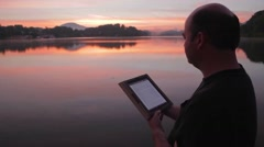 Man Reading Tablet By Lake At Sunrise Stock Footage