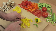 Chef dicing a yellow bell pepper on his wooden chopping board Stock Footage