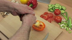 Chef slicing an orange bell pepper on his wooden chopping board Stock Footage