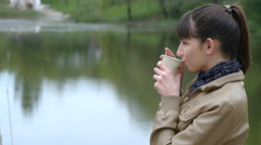 Girl stands on the embankment of the river and drinking cup of takeaway coffee Stock Footage