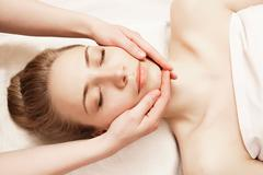 Spa. Woman enjoying anti-aging facial massage - stock photo