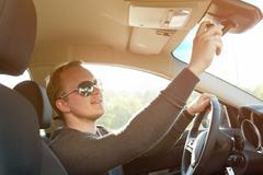 Handsome man driving car wearing  sunglasses - stock photo
