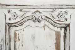 Close-up of ancient white commode bureau furniture with paint peeled off - stock photo