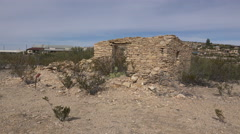 Texas Terlingua stone ruin with distant Trading Center zoom in Stock Footage