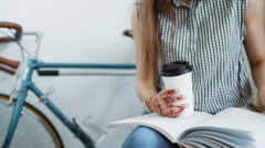Young woman sipping coffee or tea and reading magazine - stock footage