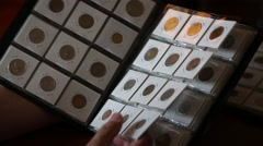 Numismatist considers coins in the album - stock footage