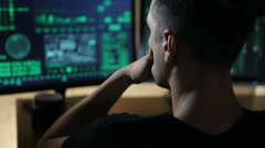 Hacker works at computer with maps and data on display screens Stock Footage