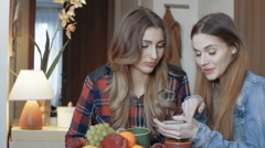 Two young female friends sitting by a table and using phone. Stock Footage