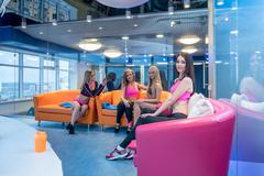 Pretty girls posing in recreational area of gym - stock photo