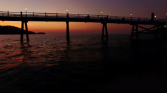 Shooting with drone at sunset in a bay. The drone passes under a pier. N. Stock Footage