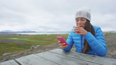 Woman outdoors using smartphone drinking coffee Stock Footage