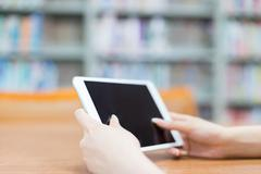 Young beautiful asian girl with tablet in school library Stock Photos