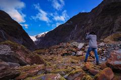 Younger female photographer take a photograph in franz josef glacier importan Stock Photos