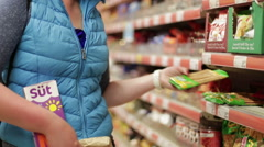 Young beautiful girl selects products in the supermarket Stock Footage