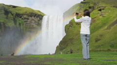 Woman tourist by waterfall Skogafoss on Iceland taking photo with phone - stock footage