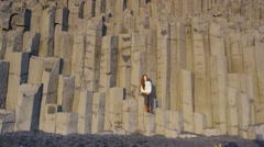 Iceland tourist at beach sitting on basalt columns Reynisfjara black sand beach Stock Footage