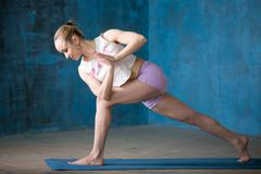 Beautiful sporty young woman doing Revolved Side Angle Pose - stock photo