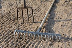 Rake and pitchfork on loosened soil closeup - stock photo
