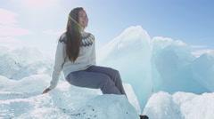 Iceland tourist at Jokulsarlon Iceberg beach sitting on icebergs on Ice beach Stock Footage