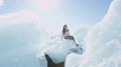 Iceland tourist at Jokulsarlon Iceberg beach sitting on icebergs on Ice beach Stock Footage