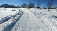 Grooming a cross country ski course, medium shot of back of snowmobile Stock Footage