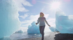 Iceland nature at Jokulsarlon Iceberg beach - Woman tourist happy running - stock footage