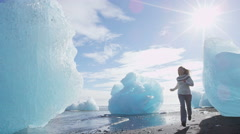 Iceland nature at Jokulsarlon Iceberg beach - Woman happy running having fun - stock footage