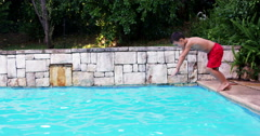 Child with red swimwear plunging on a pool Stock Footage