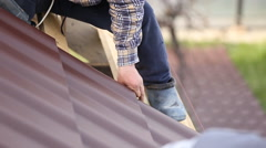 Workers install metal roofing Stock Footage