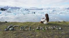 Iceland tourist enjoying Jokulsarlon glacial lagoon - ICELAND written with rocks Stock Footage