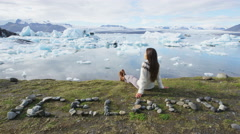 Iceland tourist enjoying Jokulsarlon glacial lagoon - ICELAND written with rocks Stock Footage