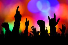 Silhouettes of concert crowd hands supporting band on stage - stock photo