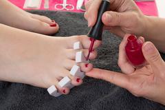 Closeup photo of a female feet at spa salon on pedicure procedure. - stock photo