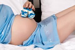 beautiful pregnant woman belly with bootees - stock photo