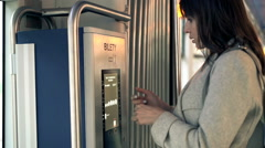 Young woman buying ticket from vending machine in tram Stock Footage