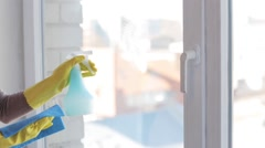 woman in gloves cleaning window with rag - stock footage