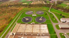 Camera flight over biogas plant from sewage treatment in green fields Stock Footage