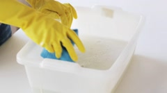 woman washing and squeezing rag in basin at home - stock footage