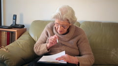 Old woman hesitating while signing papers, legal documents and contracts or will Stock Footage