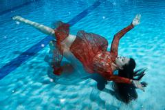 Woman in a dress drowning. - stock photo