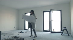 Young woman reading blueprints and checking her new home Stock Footage