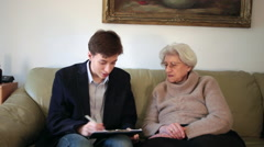 Lawyer advising elderly woman with legal matters and signing papers Stock Footage